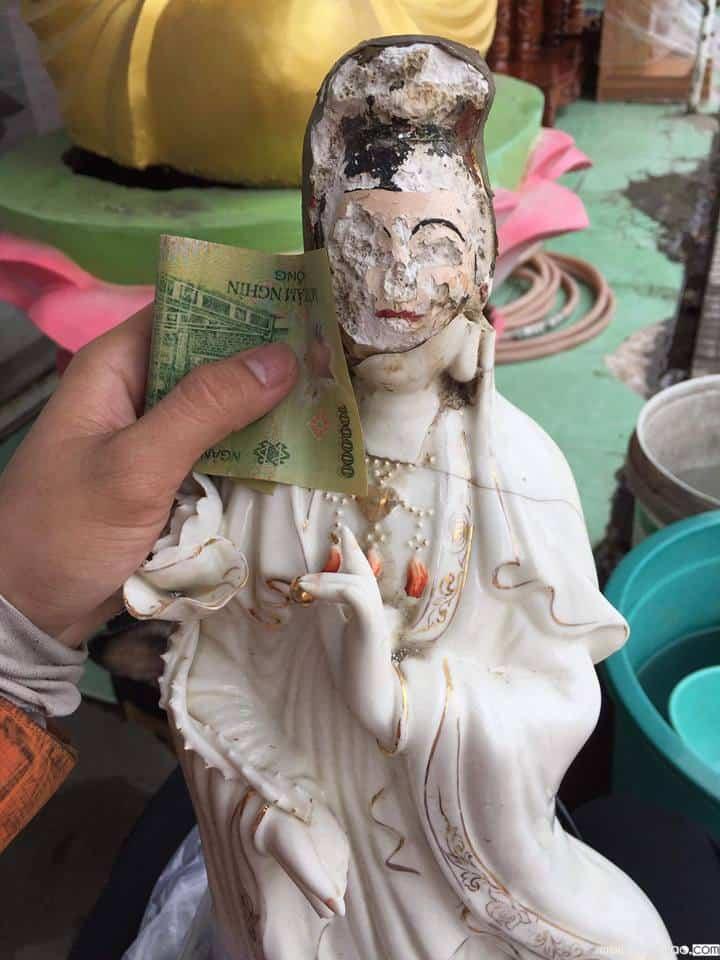 Người đàn bà và bức tượng Phật bị hư hỏng
