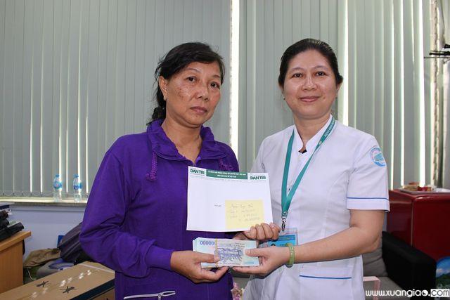 Đại diện bệnh viện trao món tiền bạn đọc giúp gia đình thông qua Báo Dân trí tuần 1 và 2 tháng 3