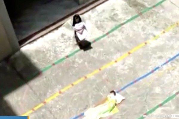 Hình ảnh cắt ra từ video, bé trai đang nằm dưới sân, còn bé gái đang đứng ôm mền