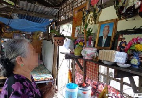 Bà N. trước bàn thờ chồng và tổ tiên gắn tạm trên vách căn chòi sửa xe đạp của người con rể. Ảnh: PLTP